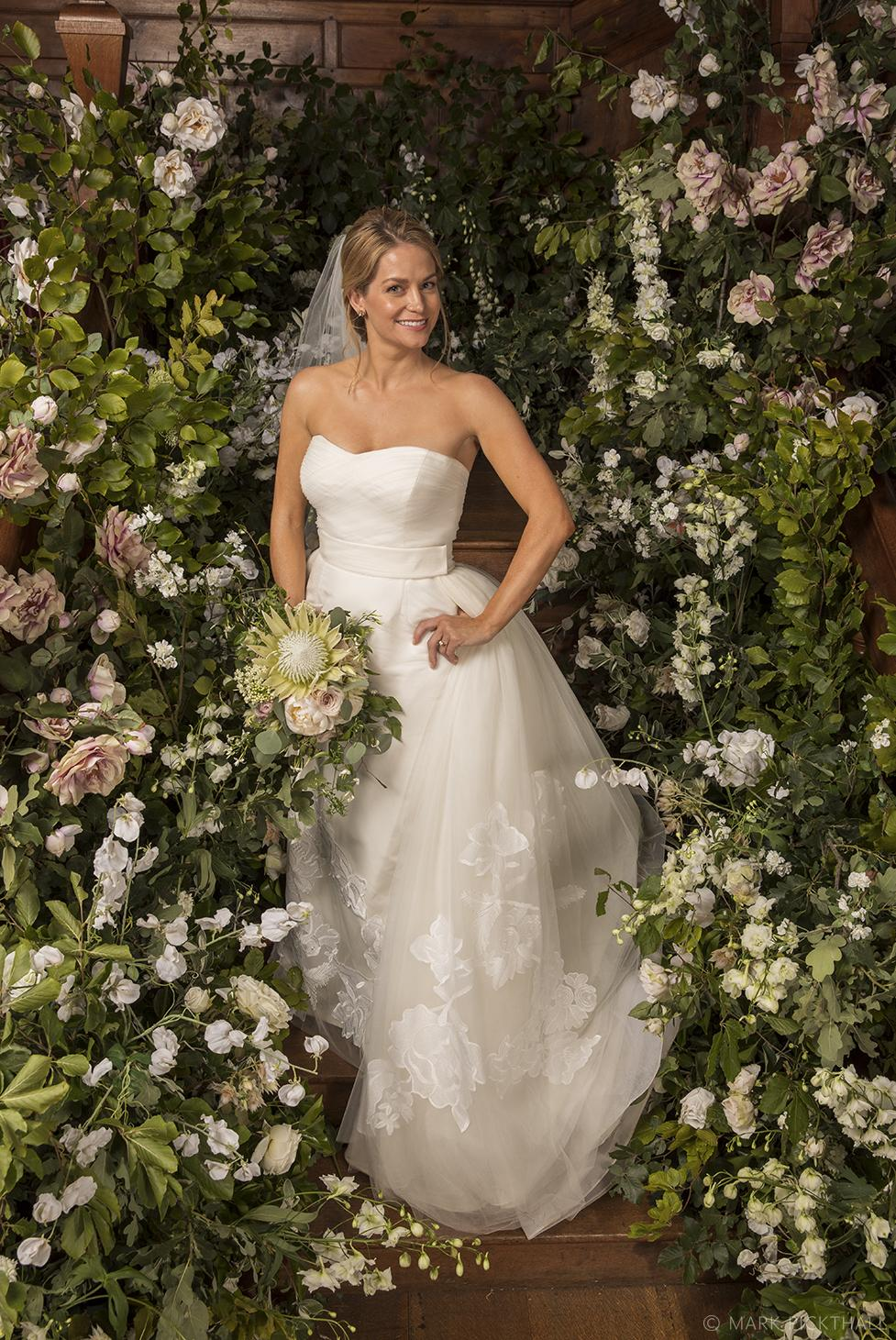 Bride standing on the staircase at North Cadbury court amidst Kitty Grayson Flowers incredible creation